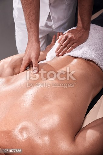 1071579572 istock photo two young man, 20-29 years old, sports physiotherapy indoors in studio, photo shoot. Physiotherapist massaging muscular patient back with his one hand close-up. 1071577866