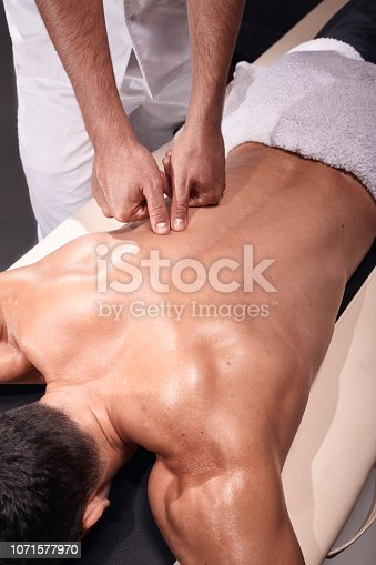 1071579572istockphoto two young man, 20-29 years old, sports physiotherapy indoors in studio, photo shoot. Physiotherapist massaging muscular patient back with his hands and fingers. 1071577970