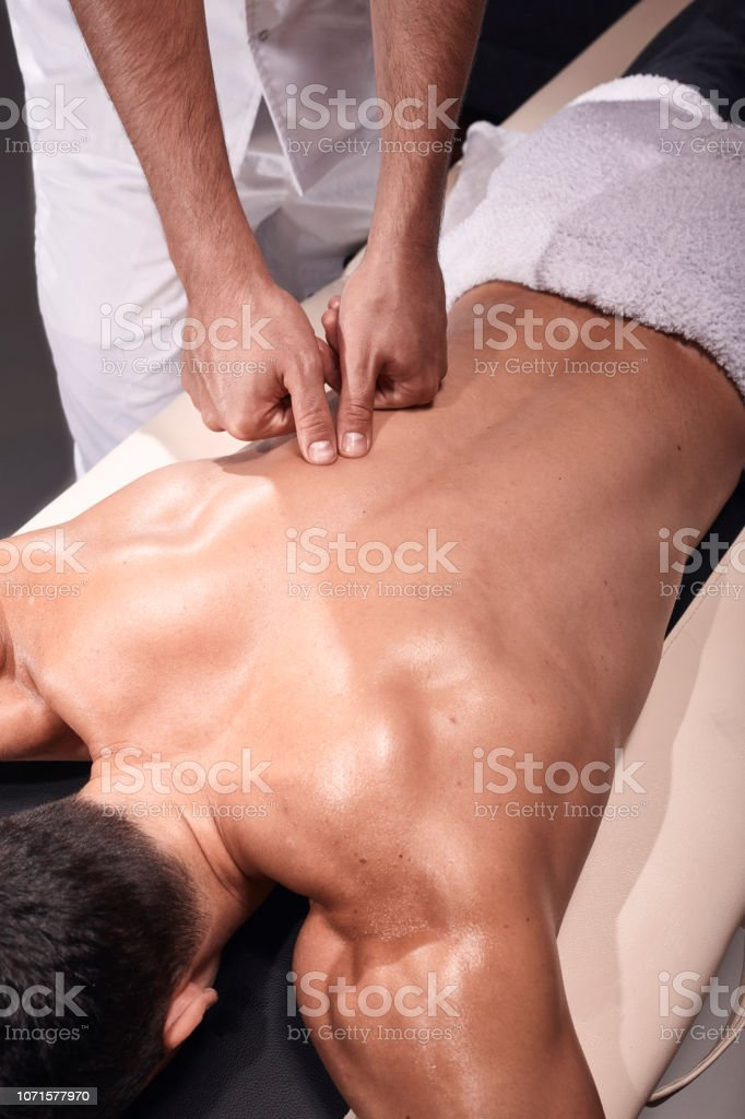 two young man, 20-29 years old, sports physiotherapy indoors in studio, photo shoot. Physiotherapist massaging muscular patient back with his hands and fingers. stock photo