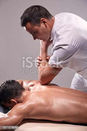 1071579572 istock photo two young man, 20-29 years old, sports physiotherapy indoors in studio, photo shoot. Physiotherapist massaging muscular patient back with his elbow. 1071578050