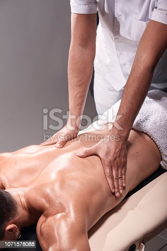 1071579572istockphoto two young man, 20-29 years old, sports physiotherapy indoors in studio, photo shoot. Physiotherapist massaging muscular patient back with his hands close-up. 1071578088