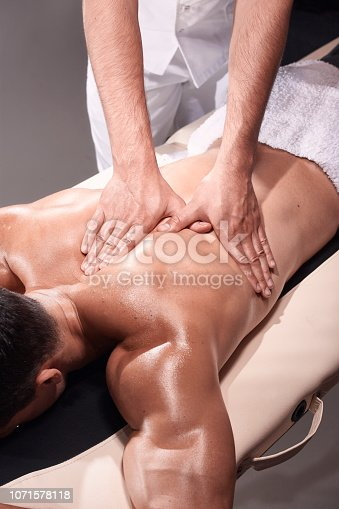 1071579572istockphoto two young man, 20-29 years old, sports physiotherapy indoors in studio, photo shoot. Physiotherapist massaging muscular patient shoulder with his hands close-up. 1071578118
