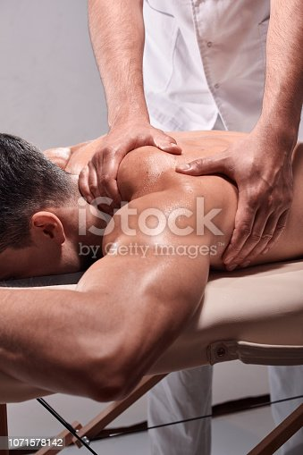 1071579572istockphoto two young man, 20-29 years old, sports physiotherapy indoors in studio, photo shoot. Physiotherapist massaging muscular patient back side of shoulder or arm, with his hands close-up. 1071578142