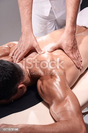 1071579572istockphoto two young man, 20-29 years old, sports physiotherapy indoors in studio, photo shoot. Physiotherapist massaging muscular patient back side of shoulder or arm, with his hands close-up. 1071578166