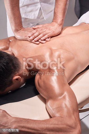 1071579572 istock photo two young man, 20-29 years old, sports physiotherapy indoors in studio, photo shoot. Physiotherapist massaging muscular patient back with his hands close-up. 1071578176