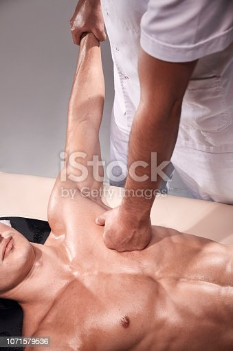 1071579572istockphoto two young man, 20-29 years old, sports physiotherapy indoors in studio, photo shoot. Physiotherapist massaging muscular patient chest abdomen with his hands, upper body shot, with abdomen. 1071579536