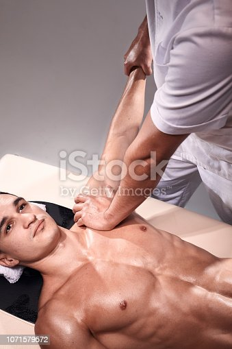 1071579572istockphoto two young man, 20-29 years old, sports physiotherapy indoors in studio, photo shoot. Physiotherapist massaging muscular patient chest abdomen with his hands, upper body shot, with abdomen. 1071579572