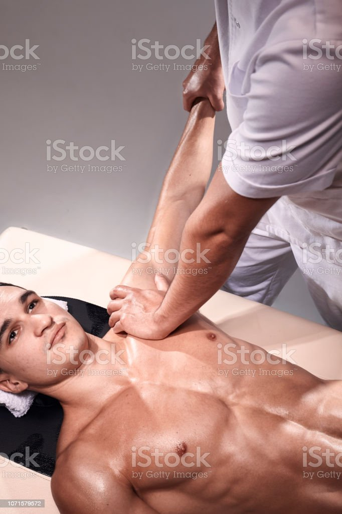 two young man, 20-29 years old, sports physiotherapy indoors in studio, photo shoot. Physiotherapist massaging muscular patient chest abdomen with his hands, upper body shot, with abdomen. stock photo