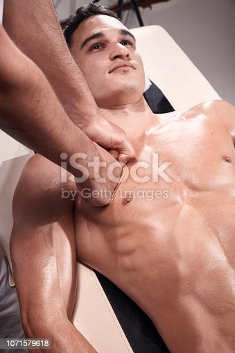 1071579572istockphoto two young man, 20-29 years old, sports physiotherapy indoors in studio, photo shoot. Physiotherapist massaging muscular patient chest abdomen with his hands, upper body shot, with abdomen. 1071579618