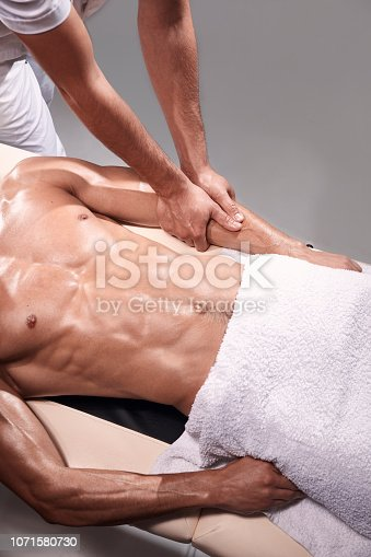 1071579572 istock photo two young man, 20-29 years old, sports physiotherapy indoors in studio, photo shoot. Therapist masseur massaging patient arms laying on his back on bed, with his hands. abdomen shot, elevated view. 1071580730