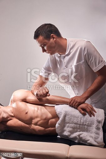 1071579572istockphoto two young man, 20-29 years old, sports physiotherapy indoors in studio, photo shoot. Therapist masseur massaging arm of muscular patient laying on his side, with elbow. 1071580782