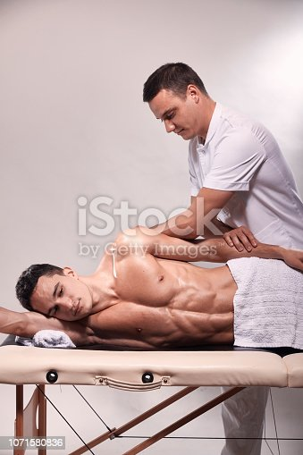 1071579572istockphoto two young man, 20-29 years old, sports physiotherapy indoors in studio, photo shoot. Therapist masseur massaging arm of muscular patient laying on his side, with elbow. 1071580836