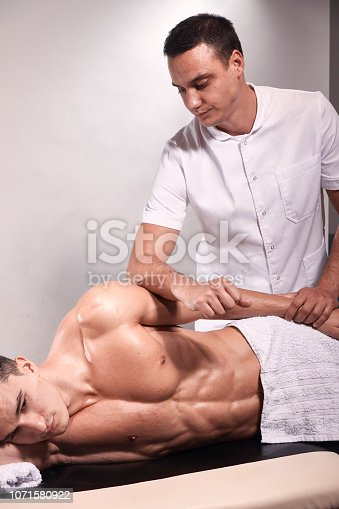 1071579572istockphoto two young man, 20-29 years old, sports physiotherapy indoors in studio, photo shoot. Therapist masseur massaging arm of muscular patient laying on his side, with elbow. 1071580922