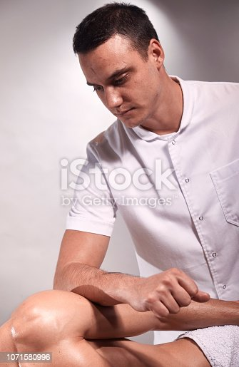1071579572istockphoto two young man, 20-29 years old, sports physiotherapy indoors in studio, photo shoot. Therapist masseur portrait, massaging arm of muscular patient laying on his side, with elbow. 1071580996