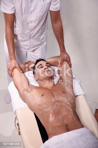 1071579572istockphoto two young man, 20-29 years old, sports physiotherapy indoors in studio, photo shoot. Therapist stretching arms and chest of muscular patient laying on his back on bed. 1071581020