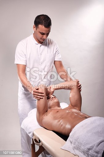 1071579572 istock photo two young man, 20-29 years old, sports physiotherapy indoors in studio, photo shoot. Physiotherapist stretching muscular patient arms with his hands. 1071581080