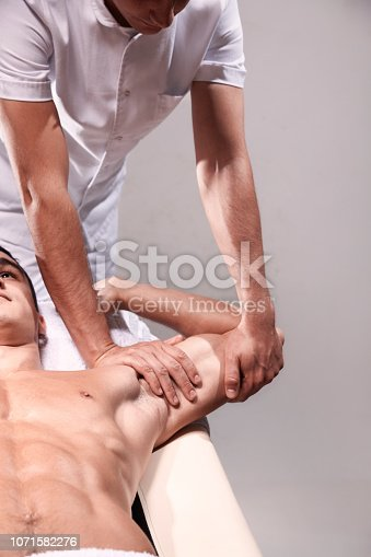 1071579572 istock photo two young man, 20-29 years old, sports physiotherapy indoors in studio, photo shoot. Physiotherapist massaging muscular patient back with his hands. 1071582276