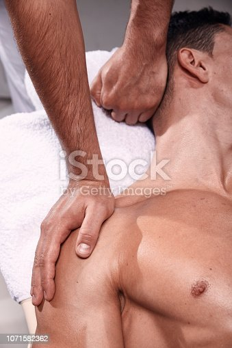 1071579572istockphoto two young man, 20-29 years old, sports physiotherapy indoors in studio, photo shoot. Physiotherapist massaging mans back. 1071582362
