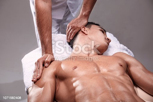 1071579572istockphoto two young man, 20-29 years old, sports physiotherapy indoors in studio, photo shoot. Physiotherapist stretching mans neck with his hands. 1071582408