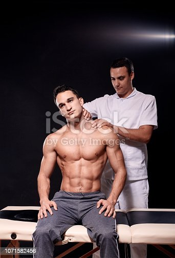 1071579572istockphoto two young man, 20-29 years old, sports physiotherapy indoors in studio, photo shoot. Physiotherapist massaging muscular patient shoulder with his hands, while he is sitting on bed. 1071582456