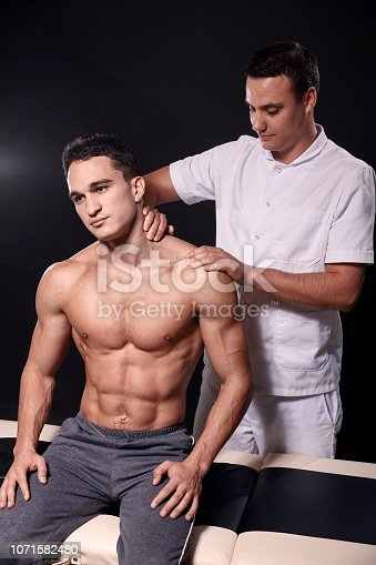 1071579572 istock photo two young man, 20-29 years old, sports physiotherapy indoors in studio, photo shoot. Physiotherapist massaging muscular patient shoulder with his hands, while he is sitting on bed. 1071582480