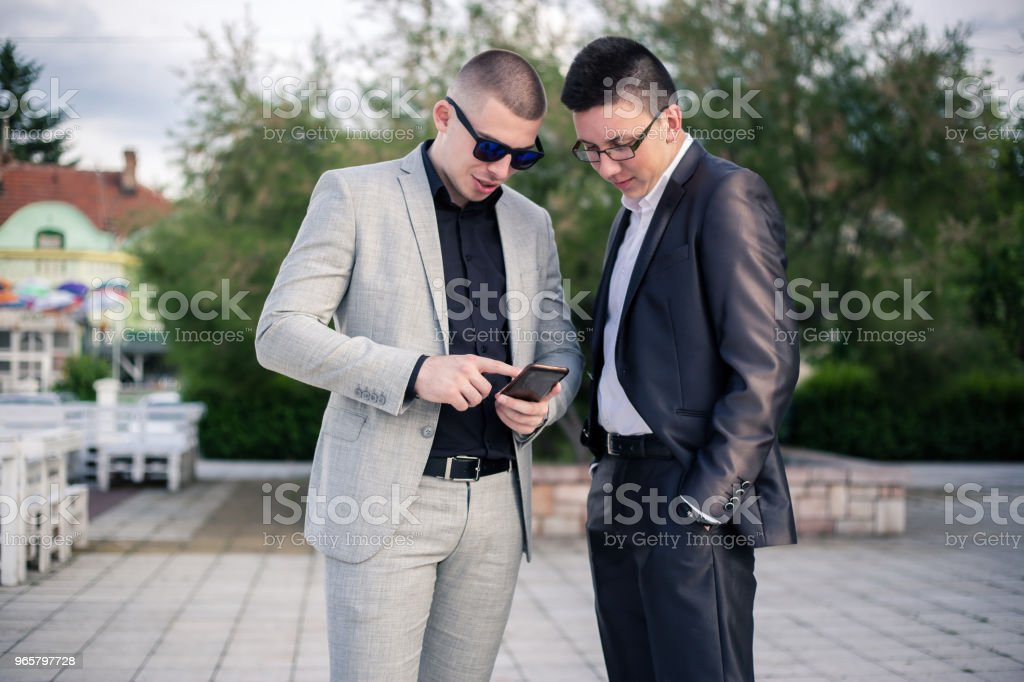 Two young man looking at mobile phone.