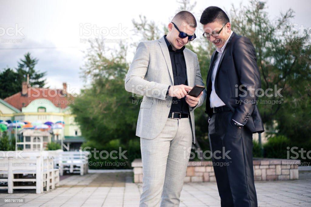 Twee jonge man kijkend naar mobiele telefoon. - Royalty-free 18-19 jaar Stockfoto