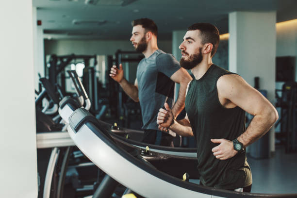 Two young man running on treadmill at gym stock photo