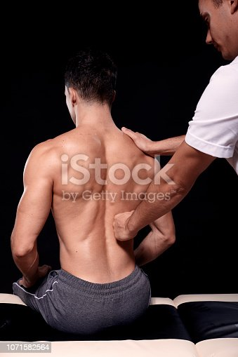 1071579572 istock photo two young men, 20-29 years old. physiotherapist massaging patients muscular back with his fist, rear view. studio shot, black background. 1071582564
