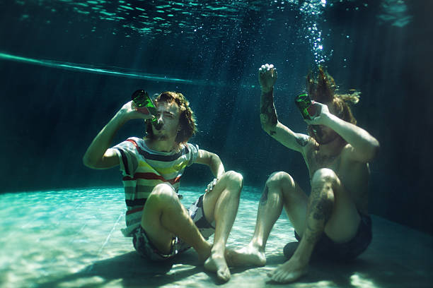 Two young men drinking beer in pool stock photo