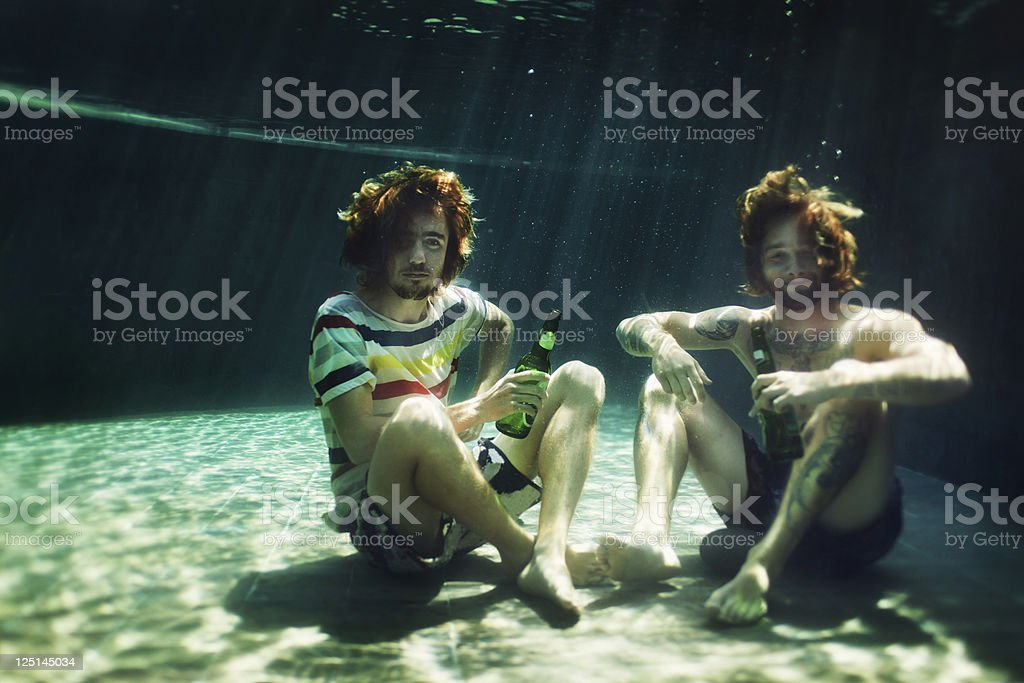 Two young men drinking beer in pool royalty-free stock photo