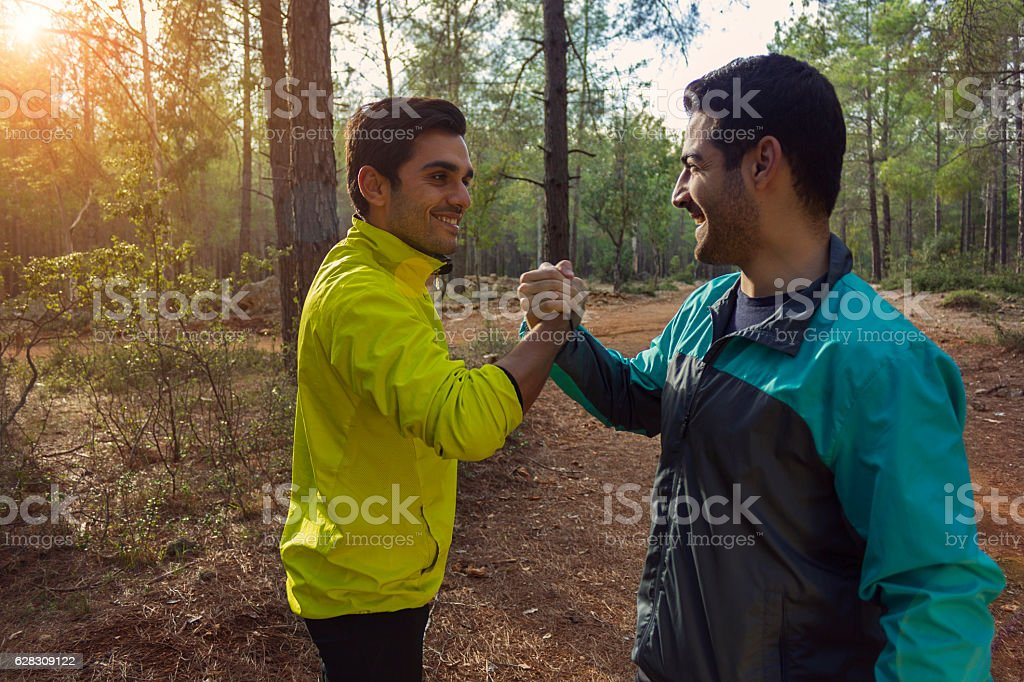 Two young men giving high five in the forest exercise stock photo