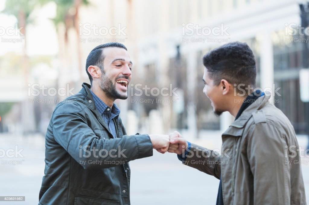 Two young men greeting on city street with fist bump stock photo two young men greeting on city street with fist bump royalty free stock photo m4hsunfo