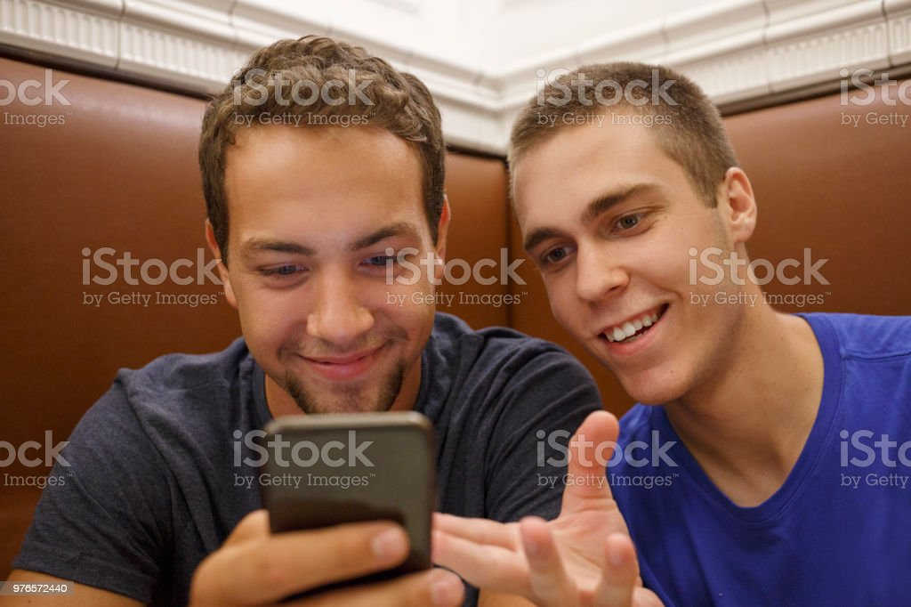 Two young men, have fun. Friends using smartphone. Casual lifestyles Urban scene Italy.  Visiting Trieste, Italy. stock photo