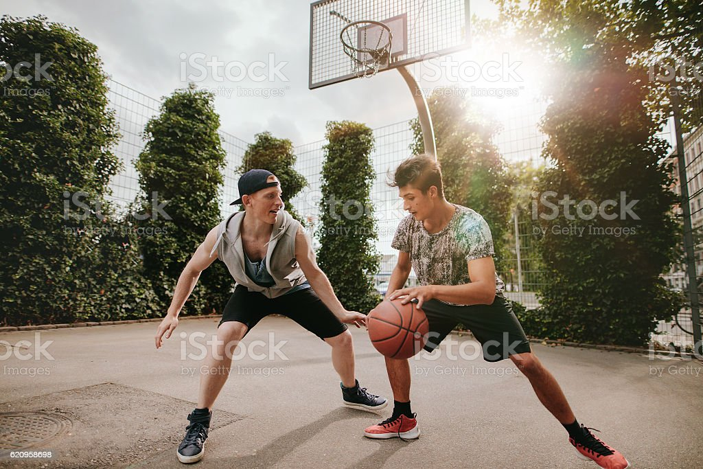 Two young men having a game of basketball stock photo