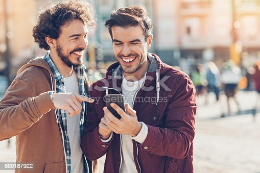 Two young men looking at a smart phone and laughing outdoors in the city