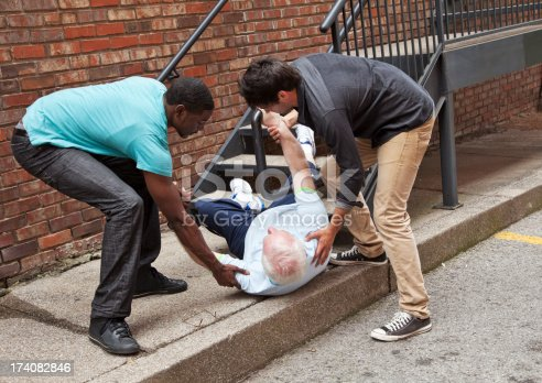 istock Two young men helping fallen down senior. Multi ethnic 174082846