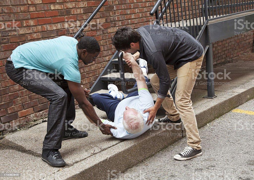 Two young men helping fallen down senior. Multi ethnic stock photo