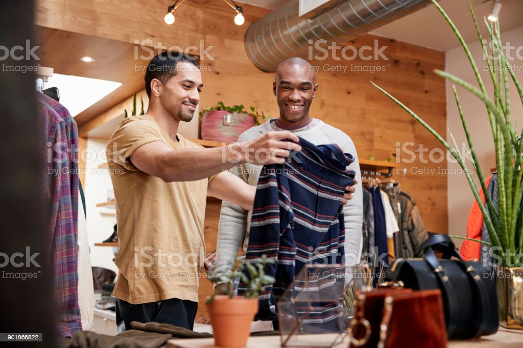 Two young men holding up clothes to look at in clothes shop stock photo