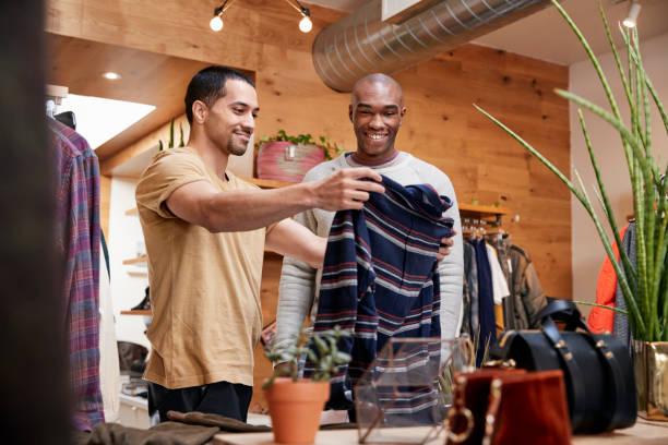 twee jonge mannen kleding te houden om te kijken naar in kleding winkel - kledingwinkel stockfoto's en -beelden