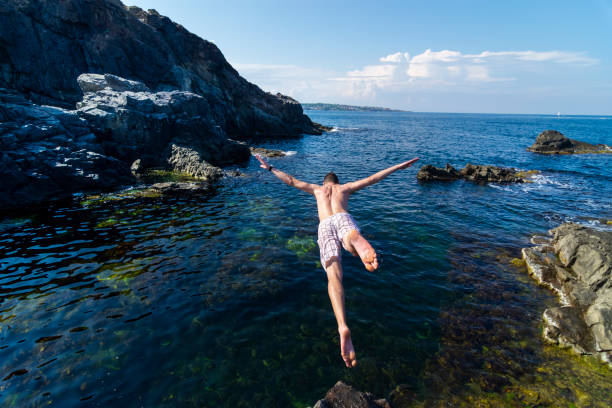 Two young men jumping off cliff into sea stock photo
