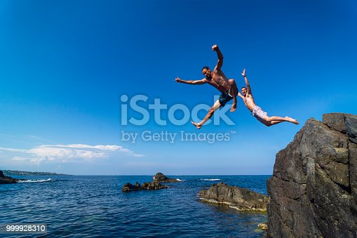Two brave divers jumping off cliff into sea