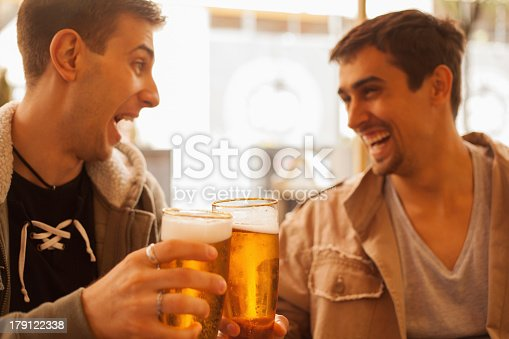 istock Two young men laughing and drinking beer together  179122338