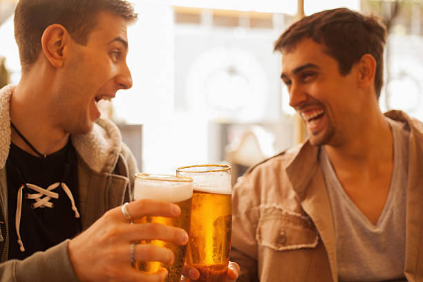 Two young men laughing and drinking beer together  stock photo