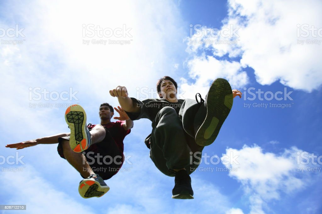 Two young men mid-air jumping, parkour performer stock photo