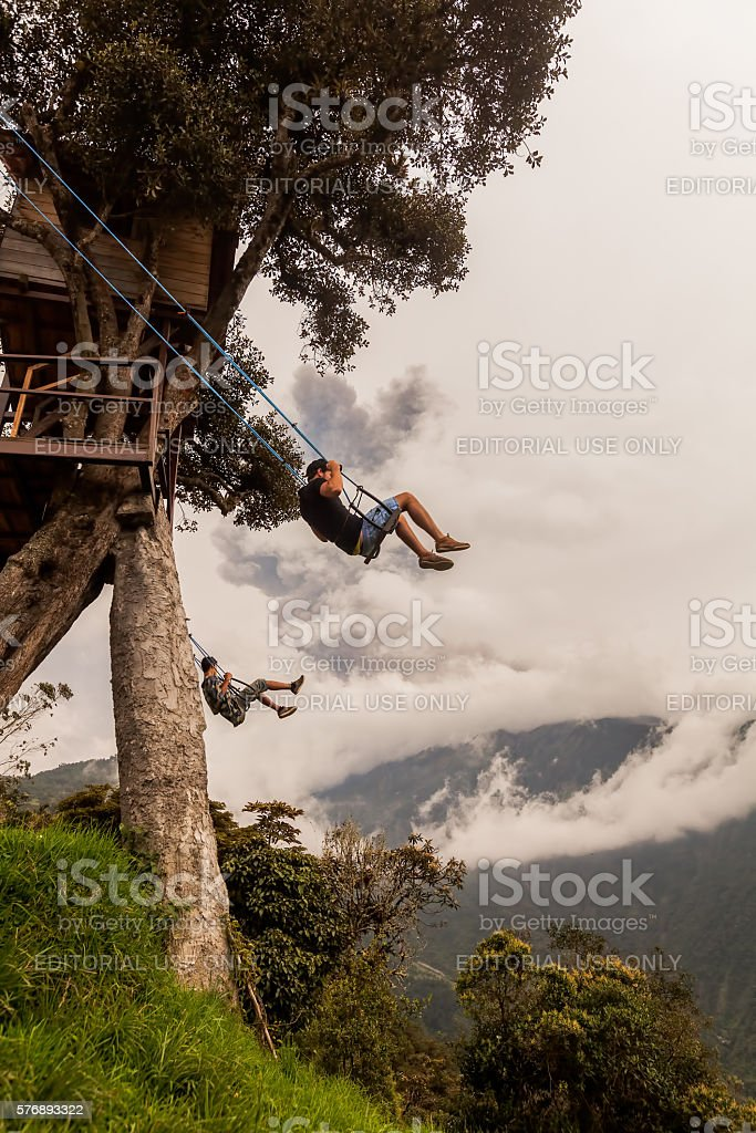 Two Young Men On A Swing In Banos stock photo