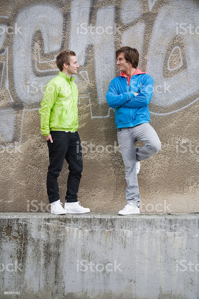 Two young men on wall royalty-free stock photo