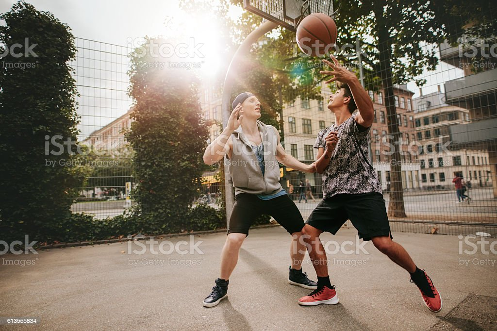 Two young men playing a game of basketball stock photo