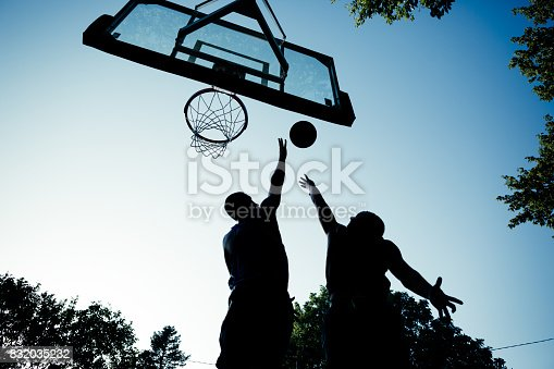 One on one, outdoor basketball. Two players practicing basketball game. Silhouetted players, one blocking the other