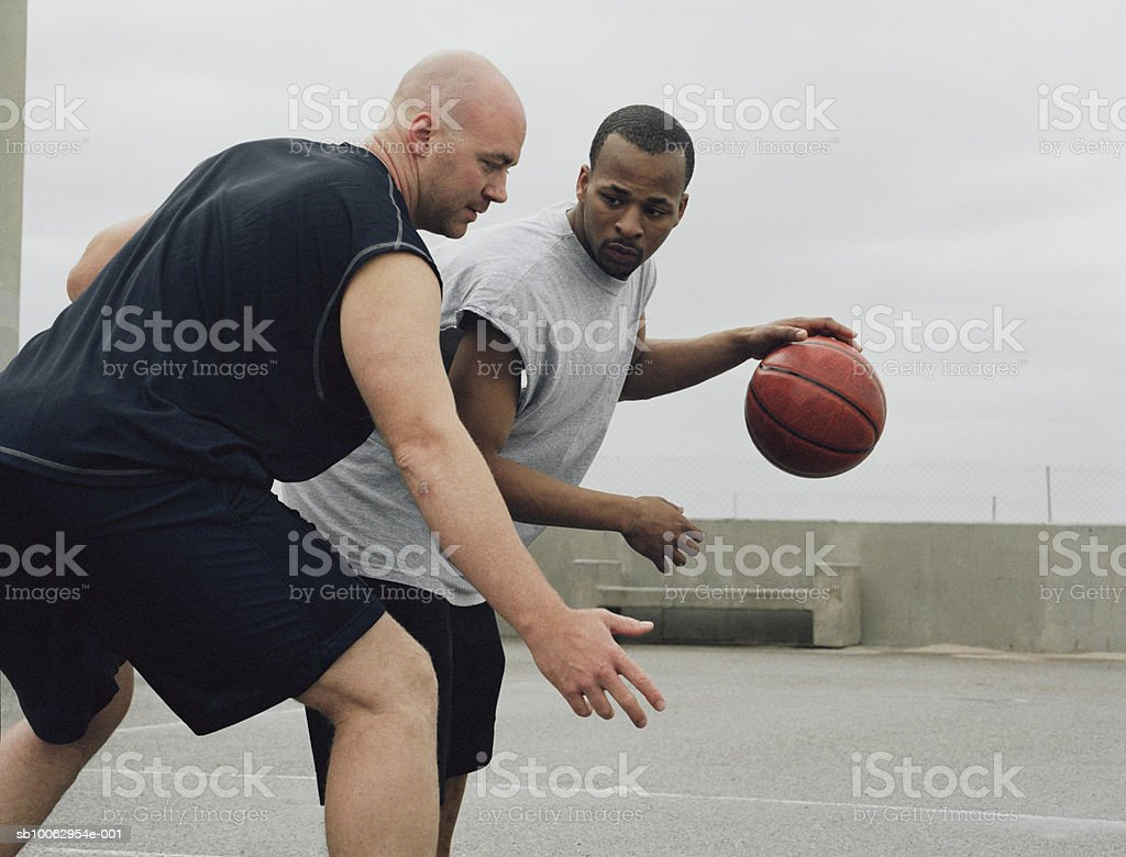 Two young men playing basketball outdoors royalty-free stock photo